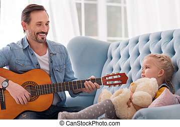 Good looking caring father singing for his daughter