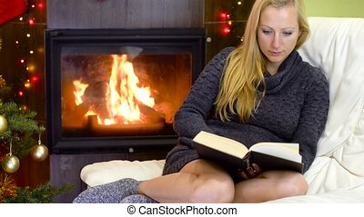 young woman reading book at christmas time in front of...