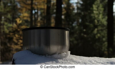Steaming cup of hot tea or coffee standing on the snow in the forest.