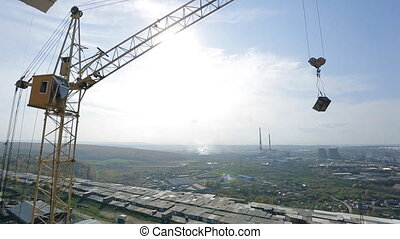 Panoramic view of industrial area with crane working on...