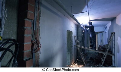 Professional welder welds metal pipe inside unfinished room.