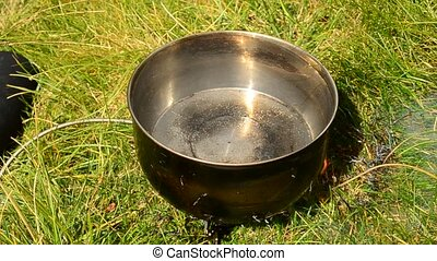 Water boiling in a saucepan on fire outdoors - Water boiling...