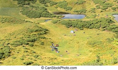 People on green field near a lake in mountains