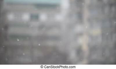 Snow falling on blurred urbank background of apartment block