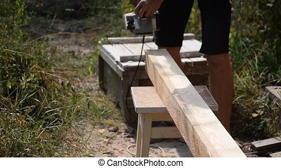 Carpenter planes a beam with wood planer