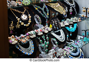 Variety of jewelry in store window. rings, necklaces, bracelets and earrings on velvet stands for sale.