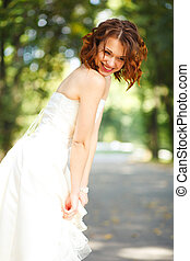 Shy and smiling - bride looks down at the ground while she...