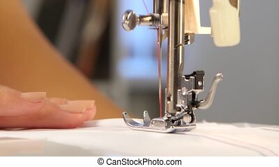 Sew a white cloth. Close up - Sew a white cloth, woman sews...
