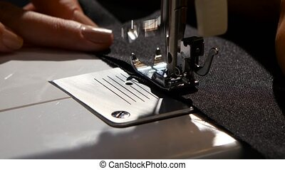 Sew black fabric. Close up - Sew black fabric, woman sews on...