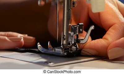 Sew. Close up - Sew, woman sews on the sewing machine, the...