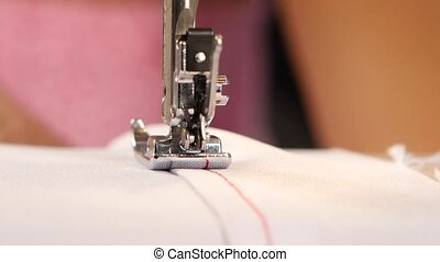 Red stitching on white cloth. Close up