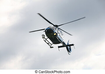 Police helicopter - Blue and silver police helicopter flying...