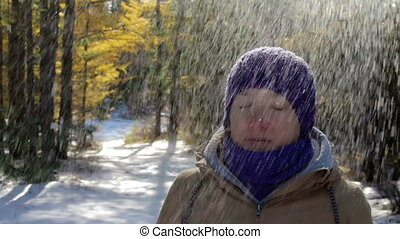 Snow falls from the trees onto the head of the girl in the winter forest