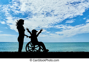 Happy boy in a wheelchair and a nurse at the sea day
