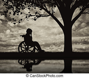 Disabled child in a wheelchair crying near tree on beach