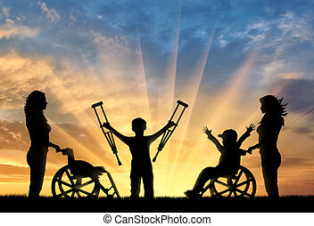 Happy boy in wheelchair and boy standing with crutches disabled person and nurses sunset