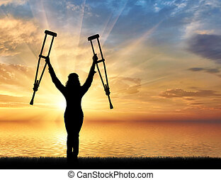 Happy disabled on beach and holding his crutches sunset....