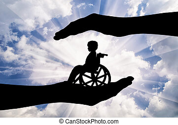 Disabled child in a wheelchair in the hands of man