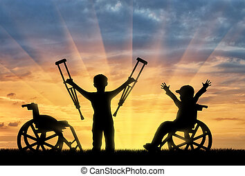 Happy boy in wheelchair and boy standing with crutches disabled person sunset