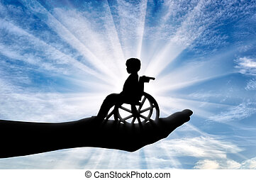 Disabled child in a wheelchair in a man's hand