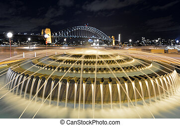 Water fountain against Sydney Harbour Bridge at night