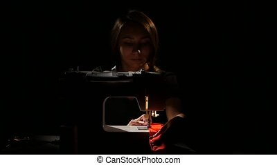 Girl sews on a black background. Close up