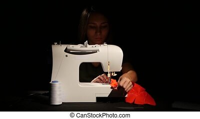 Girl sews on the sewing machine. Close up - Girl sews on the...