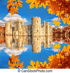Historic Bodiam Castle with autumn leaves in East Sussex,...