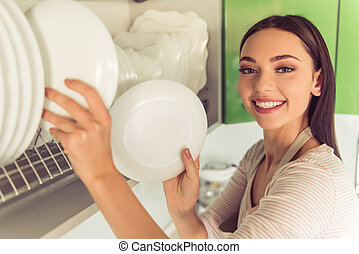 Woman cleaning her kitchen - Beautiful young woman in apron...