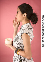 Skincare - Chinese girl in white cheongsam applying cream on...