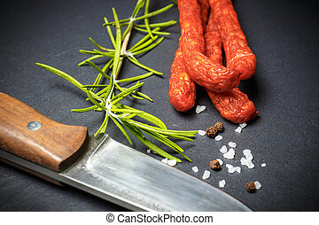 Closeup of fresh thin sausages on black stone background...