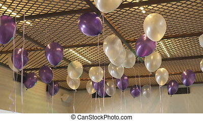 White and purple balloons floating on the ceiling for...