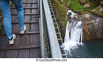 Person crossing a high bridge over a waterfall