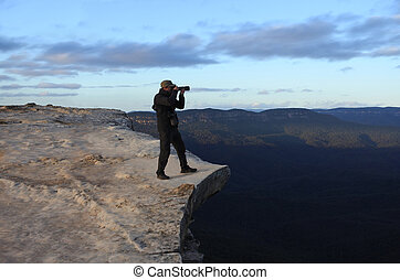Man photographing the landscape from Lincoln Rock Lookout at sunrise of the Grose Valley located within the Blue Mountains New South Wales Australia