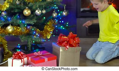 cute boy open his present at christmas tree near the...