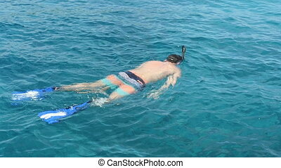 Snorkelling in the clear turquoise water - Young man...