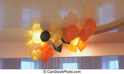 Red, yellow balloons floating on the ceiling for birthday...