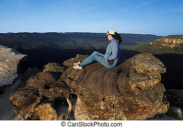 Woman looks at the landscape from Lincoln Rock Lookout at sunrise of the Grose Valley located within the Blue Mountains New South Wales Australia