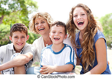 Mother with grown up daughter and son in the park smiling...