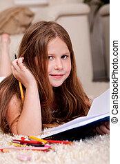 Closeup of cute little girl doing her homework - An...