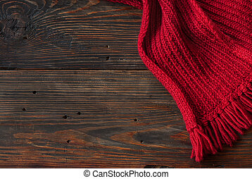 Knitted scarf - Red Knitted scarf on wooden background, with...