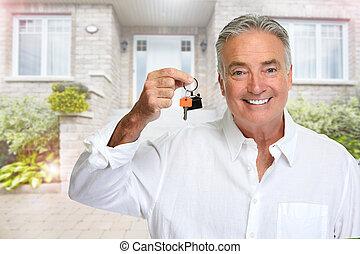 Senior man with house key. - Smiling happy elderly man...