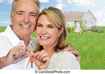 Senior couple with house key. - Smiling happy elderly couple...