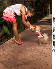 Black woman dancing with Pomeranian Spitz dog focus on dog -...