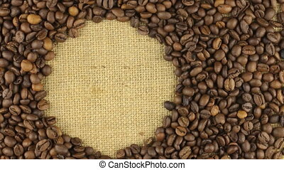 Rotation of the coffee beans lying on sackcloth with space for your text