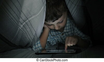 Little boy using tablet - Little boy lying on the bed in the...