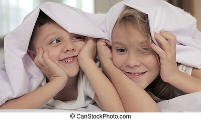 Lovely brother and sister lying in bed at home. Concept of...