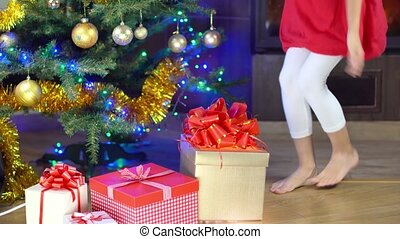 cute girl open present at christmas time near the fireplace