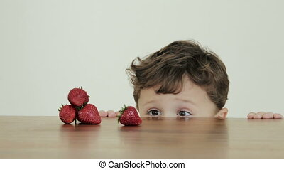 cute little boy wants to eat strawberry at the daytime