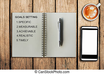 Goal setting as memo on notebook and coffee cup with mobile...